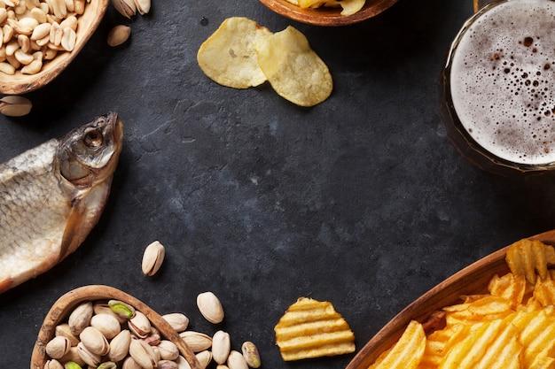 Birra chiara e snack sul tavolo di pietra Foto Premium