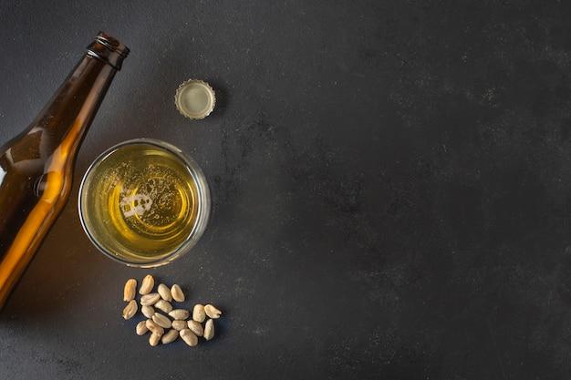 Birra vista dall'alto su vetro e bottiglie con arachidi accanto Foto Gratuite