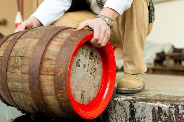 Birraio con botte di birra nel birrificio Foto Premium