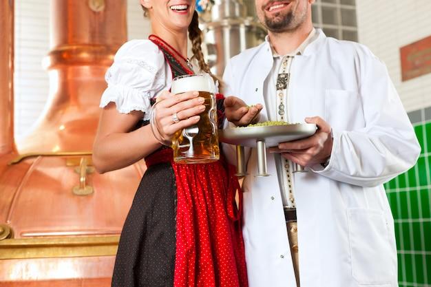 Birraio e donna con un bicchiere di birra nel birrificio Foto Premium