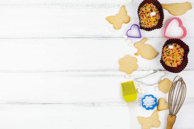 Biscotti a forma di animali con utensili da cucina sul tavolo di legno Foto Gratuite