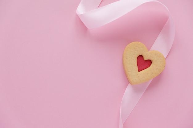 Biscotti a forma di cuore con un nastro rosa su un rosa Foto Premium