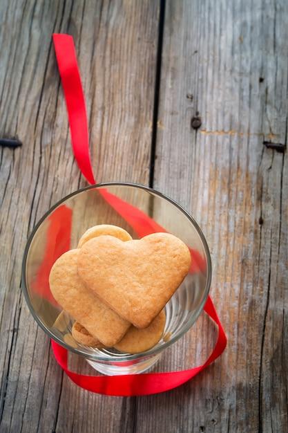 Biscotti a forma di cuore in un bicchiere. san valentino sfondo Foto Premium