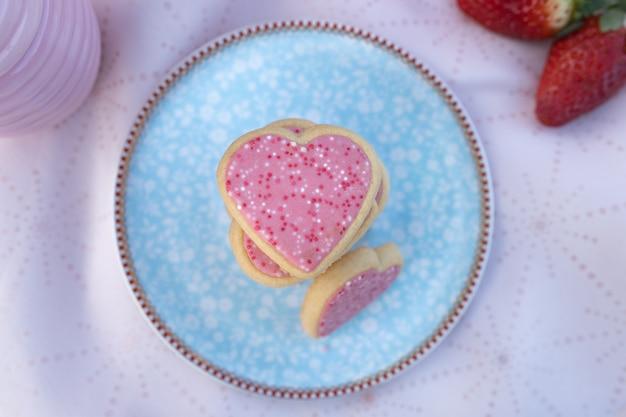 Biscotti a forma di cuore rosa sul piatto decorato Foto Premium