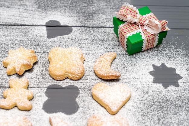 Biscotti a forma di differenti di natale con la polvere dello zucchero e contenitore di regalo sulla tavola di legno Foto Premium