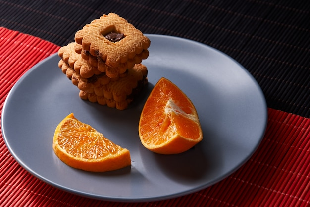 Biscotti al cioccolato e pezzo di arancia sul piatto e su rosso e nero Foto Premium