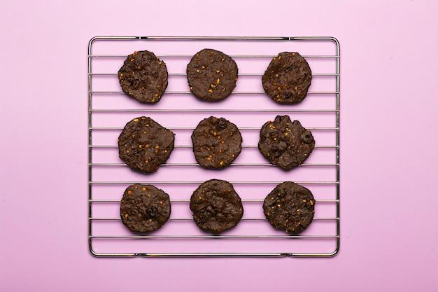 Biscotti al cioccolato senza glutine fatti in casa con cereali, noci e cacao biologico. biscotti e pasticcini da farina di segale su uno sfondo colorato. concetto senza glutine Foto Premium