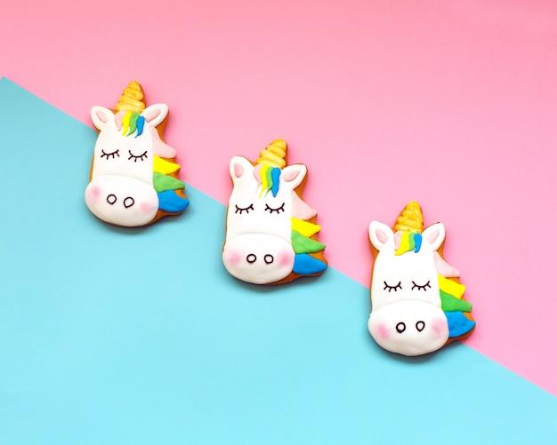 Biscotti allo zenzero a forma di un unicorno su carta pastello geometrica Foto Premium