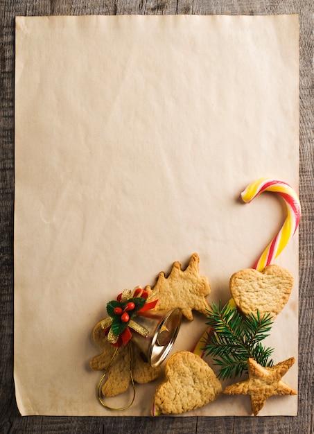 Biscotti allo zenzero di natale con rami di abete sulla carta da imballaggio. Foto Premium
