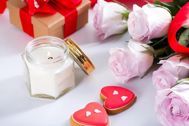 Biscotti casalinghi del cuore di giorno di biglietti di s. valentino, rose rosa e candela sulla tavola bianca Foto Premium