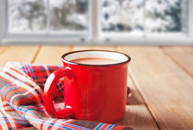 Biscotti con la tazza rossa della tavola di legno calda del caffè o del tè con la finestra congelata sul. concetto caldo e accogliente invernale Foto Premium