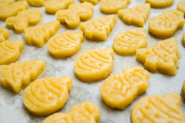 Biscotti crudi di natale del pan di zenzero della pasta per childrenin sotto forma di palla, abete, pupazzo di neve Foto Premium