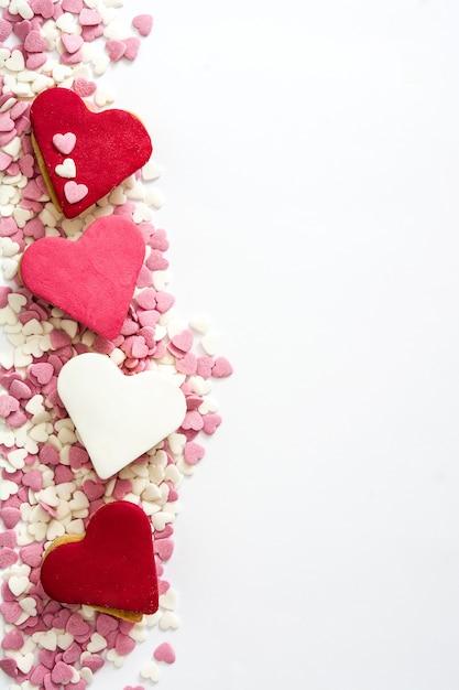 Biscotti del biglietto di s. valentino con forma del cuore isolata su superficie bianca Foto Premium