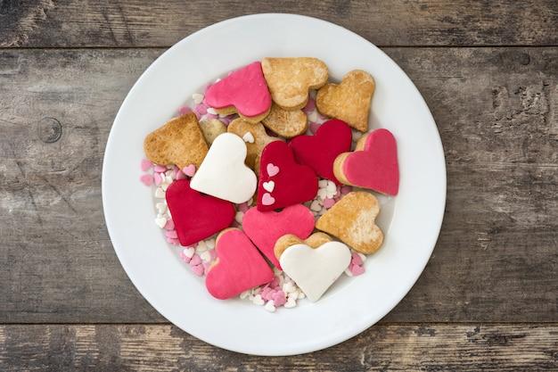 Biscotti del biglietto di s. valentino con forma del cuore sulla vista superiore della superficie di legno Foto Premium