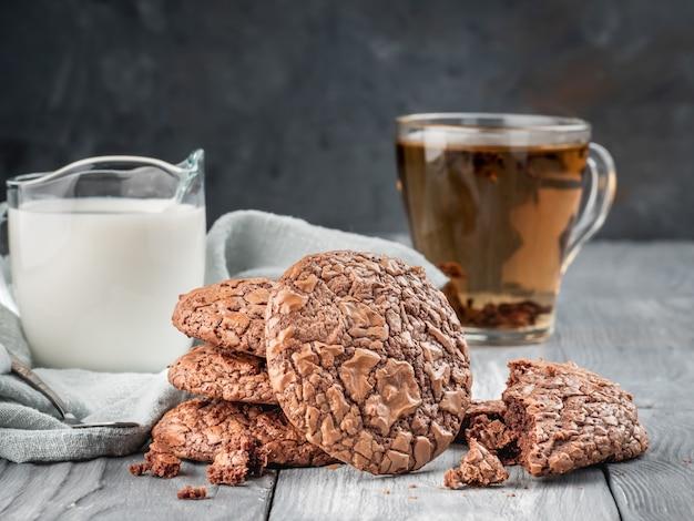 Biscotti del brownie su una tavola di legno con tè e latte. copia spazio. Foto Premium