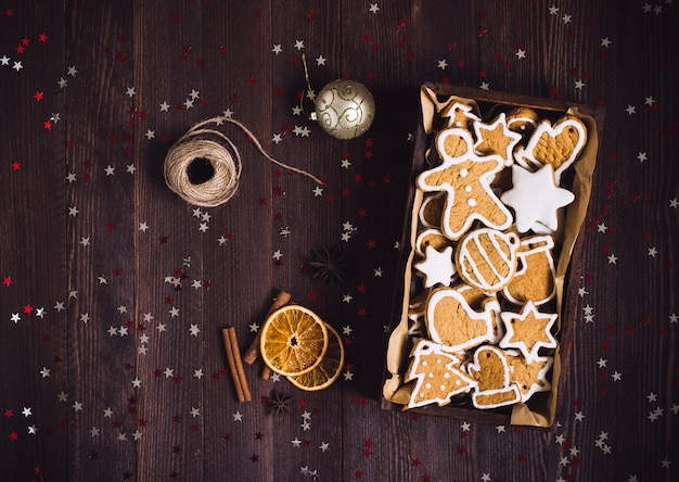 Biscotti del pan di zenzero di natale in foto scura di vista superiore della pasticceria del regalo della scatola di legno Foto Gratuite