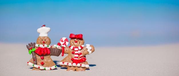Biscotti dell'uomo di pan di zenzero di natale su una spiaggia sabbiosa bianca Foto Premium