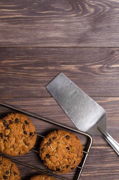 Biscotti di avena fatti in casa su rack di raffreddamento. fondo in legno fla Foto Premium