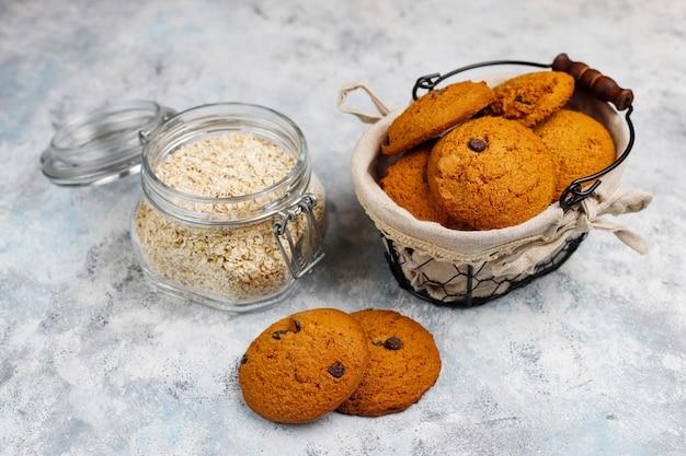 Biscotti di farina d'avena casalinghi con gocce di cioccolato su calcestruzzo Foto Gratuite