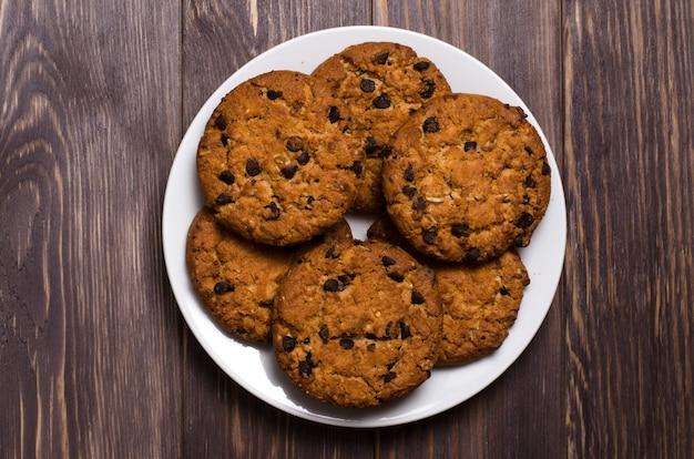 Biscotti di farina d'avena casalinghi su un piatto bianco. fondo in legno Foto Premium
