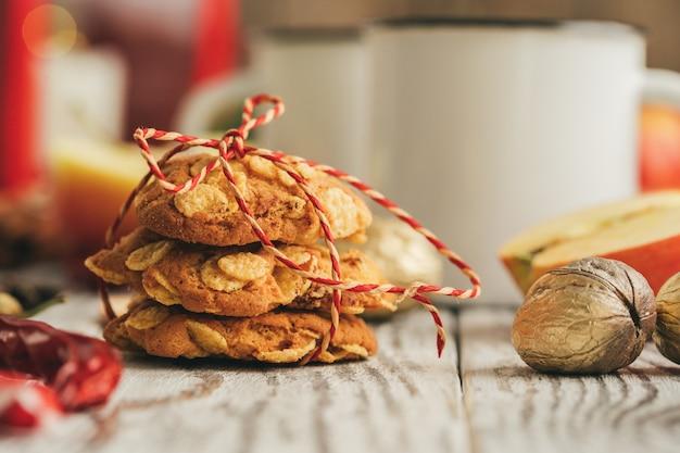 Biscotti di farina d'avena su un vecchio di legno con i bastoni e le decorazioni di cannella Foto Premium