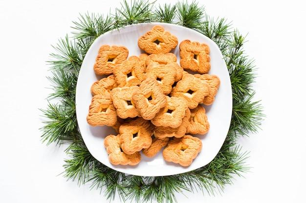 Biscotti di natale su un piatto su priorità bassa bianca Foto Premium