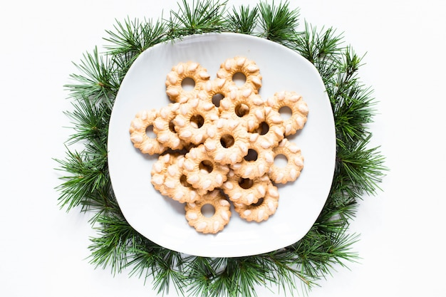 Biscotti di natale su un piatto su superficie bianca Foto Premium