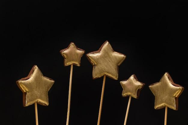 Biscotti di pan di zenzero a forma di stella colorati oro su un bastone sul nero Foto Premium