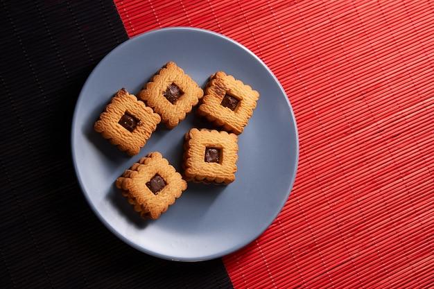 Biscotti di pepita di cioccolato impilati sul piatto grigio di stile sulla tavola di legno rossa e nera Foto Premium