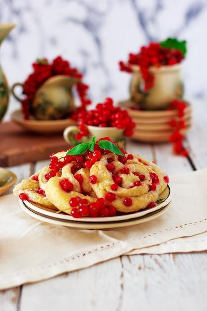 Biscotti di ricotta rotoli con ribes rosso sul piatto in ceramica con set da tè o caffè in ceramica vintage, ora del tè, colazione, dolci estivi Foto Gratuite