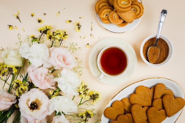 Biscotti e tè in posa piatta Foto Gratuite