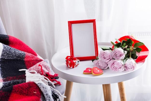 Biscotti fatti in casa del cuore di san valentino, rose rosa e cornice rossa sul tavolo bianco con sedia e plaid rosso Foto Premium