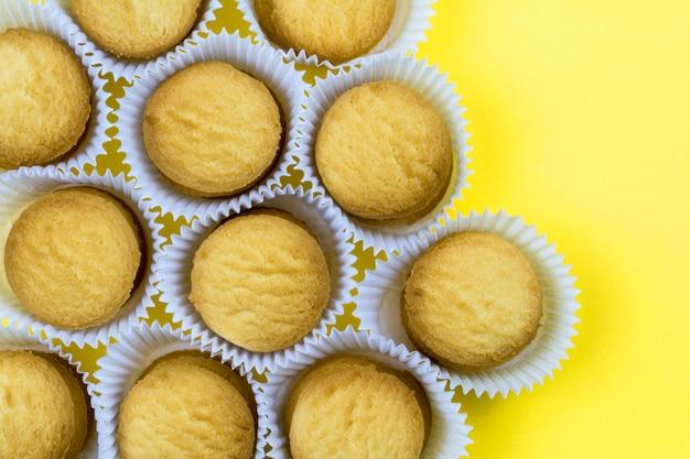 Biscotti in cestini di carta su sfondo giallo Foto Premium