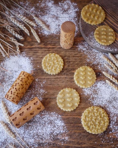 Biscotti timbrati con una stampa di cuori e farfalle. mattarelle in legno per biscotti Foto Premium