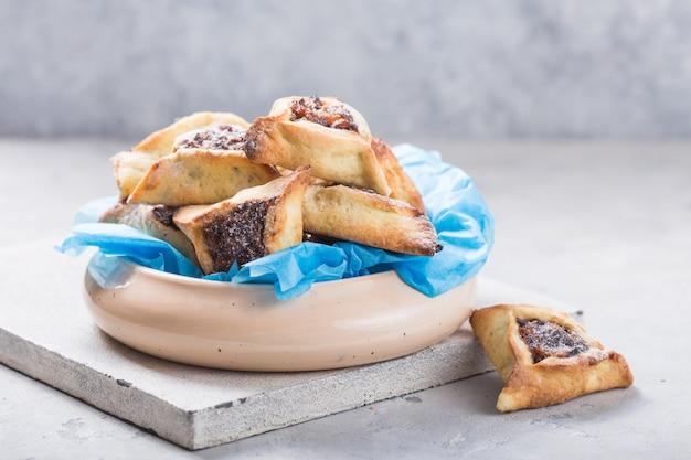Biscotti tradizionali ebraici hamantaschen con albicocche secche, datteri. concetto di celebrazione purim. Foto Premium