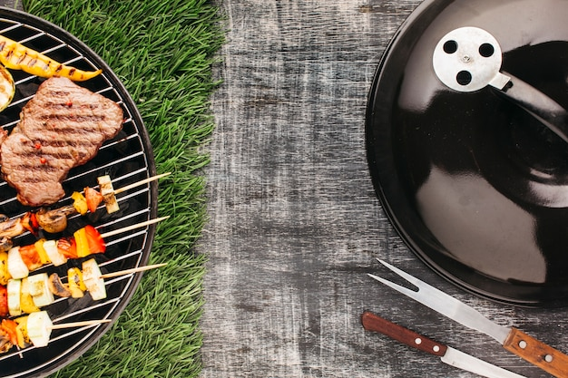 Bistecca alla griglia e spiedini di carne sulla forcella metallica grill barbecue Foto Gratuite