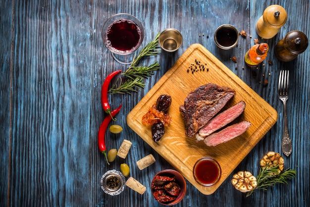 Bistecca alla griglia rara media affettata su fondo di legno rustico con rosmarino e spezie Foto Premium