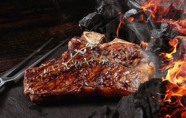 Bistecca di barbecue su una tavola di ardesia nera con forchetta e carboni grigliate Foto Premium