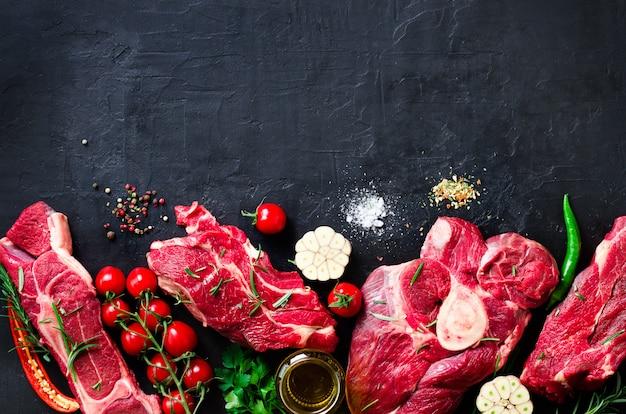 Bistecca di carne fresca cruda con pomodorini, peperoncino, aglio, olio ed erbe aromatiche Foto Premium