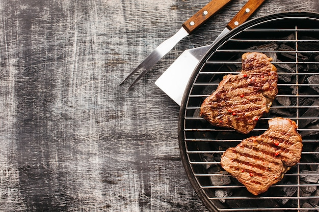 Bistecca di contorno fritto sulla griglia del barbecue sul vecchio contesto Foto Gratuite
