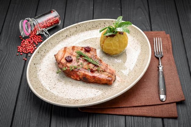 Bistecca di maiale con salsa di ciliegia e zenzero con ingredienti su sfondo disordinato vestirono. Foto Premium