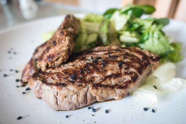 Bistecca di manzo alla griglia con insalata sul lato del giardino Foto Gratuite