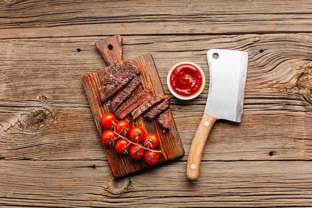 Bistecca di manzo alla griglia con salsa di pomodoro fresco sul tagliere Foto Gratuite