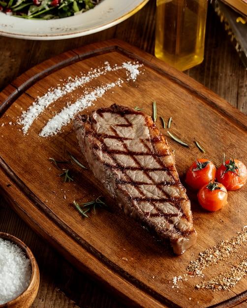 Bistecca di manzo alla griglia servita con erbe salate e pomodoro grigliato Foto Gratuite