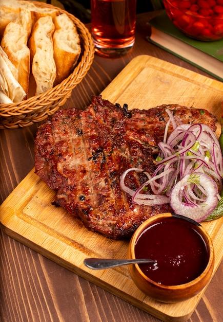 Bistecca di manzo con barbecue, salsa barbecue ed erbe aromatiche, insalata di cipolle, pepe alla griglia e pomodoro sul piatto di legno Foto Gratuite
