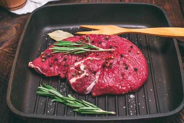 Bistecca di manzo crudo su una padella nera di quart Foto Premium