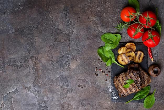 Bistecca di manzo e verdure grigliate sul bordo di ardesia sul tavolo di pietra. Foto Premium