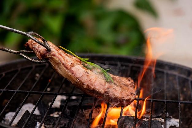 Bistecca di manzo sulla griglia griglia, fiamme su sfondo Foto Premium