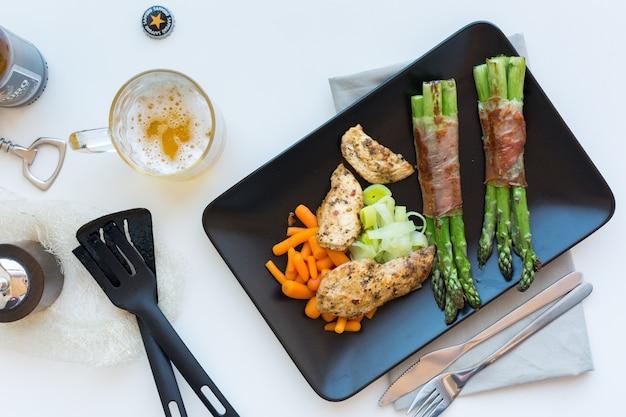 Bistecca di petto di pollo con asparagi avvolti in pancetta Foto Gratuite