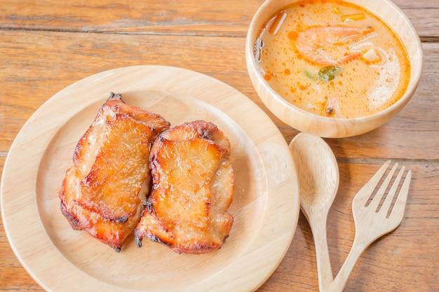 Bistecca di pollo e zuppa piccante sul tavolo di legno Foto Premium